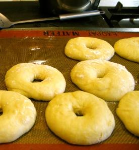 Stap 1 : maak het bageldeeg (recept volgt). Verdeel in 12 porties, maak er een bolletje met een holletje van en laat 20 minuten rijzen op een ingeoliede bakplaat.