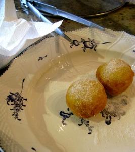 De beignets in poedersuiker wentelen (poedersuiker is geen bloemsuiker maar heel fijn kristalsuiker).