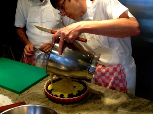 Clafoutis met kersen in voorbereiding...de ene heeft de kersen één ontpit, de andere heeft het beslag gemaakt.