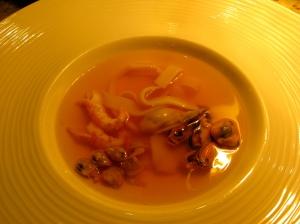 Bouillon-baisse als voorgerecht, een geklaarde bouillabaisse met schaal-en  schelpdieren.
